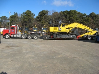 """This 105-ton capacity ROGERS® trailer easily hauls a drill rig, a crawler excavator and other oversized/overweight equipment while maintaining the 13'6"""" overhead clearance required for crossing bridges in the New York City area.  The wheels of this loader rest in wheel wells, which saves four inches of overhead clearance."""