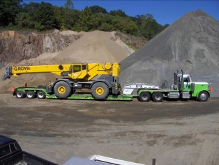 The same Rogers® 55-ton trailer hauls a Cat rubber-tire loader and a Grove rough terrain crane, plus many other pieces of heavy equipment for Stone Industries.