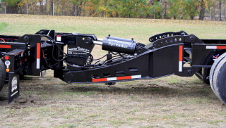 The optional Nitro-Stinger (a type of booster axle assembly) not only satisfies the spread axle permit requirements of many states but provides constant weight distribution to the rear axles.  A knuckle assembly in the booster frame assists in the trailer's maneuverability while moving forward.  The knuckle can be locked in place and the rear axles raised hydraulically to assist in moving the trailer in reverse.