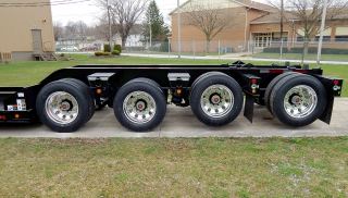 Wide trunnions between the tires provide additional load space on the trailer's rear frame.  The 3rd and 4th axles are shown in the lifted position using the axle air lift on each.  Polished aluminum disc wheels (outer only - steel inner) are optional equipment that reduces weight while enhancing the appearance of the trailer.  Optional LED amber marker/clearance lights are mounted below each trunnion.   The toggle switch for the optional LED oval amber strobe lights is located on the side of each rear channel - on the rear frame and on the removable/flip axle.