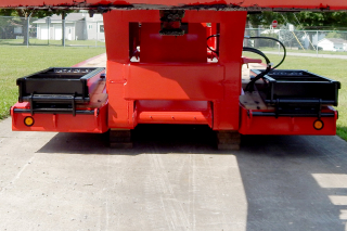 Wood-covered front folding ramps are laterally adjustable and extra long to minimize approach angle when loading or unloading machinery.