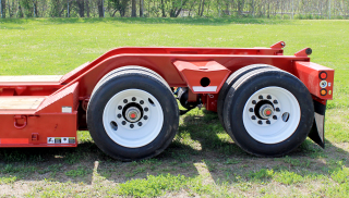 Sloped 30° bridge ramps give easy loading access to the rear frame of the trailer.  Wide trunnion outriggers between the tires provide a strong, stable loading position for various machines.