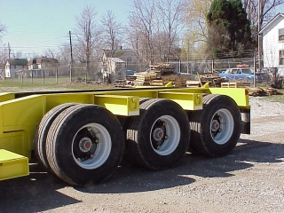 The rear frame is equipped with a severe-duty tri-axle spring/walking beam suspension and spoke type wheels.  The large outriggers have lashing D's on each end for securing tie downs.