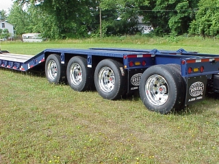The tri-axle has reinforced tread plate wheel covers.  A Removable 4th axle helps the trailer meet state weight regulations where needed.  ROGERS blue enamel finish.