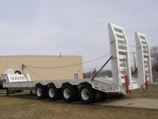 Steel covered beavertail with half-inch plate and traction bars Hydraulic powered support legs for loading over beavertail Hydraulic powered rear ramps Electric back-up alarm
