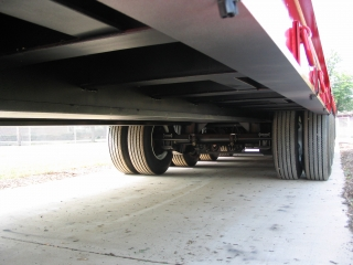 The trailer uses large main beams fabricated out of 100,000 lb. minimum yield steel and extra deep cross members to carry the load with less tare weight.