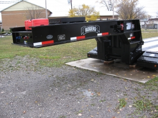 The gooseneck has a self-contained 18 HP gas engine with an independent gas tank (red container) and a tire carrier located on top (pictured without a tire).