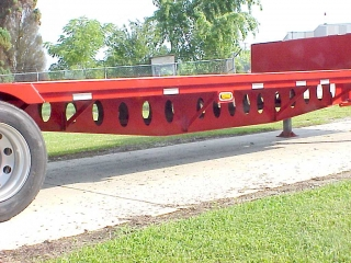 Fabricated main beams are deeper than normal for greater carrying capacity with less weight.  The cut-out holes reduce weight without compromising strength.